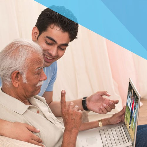 Ein junger Mann erklärt einem Senior den Umgang mit einem Laptop.