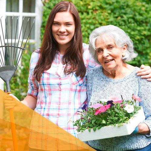 Eine junge Frau mit Rechen in der Hand hält eine Seniorin im Arm. Beide lächeln.