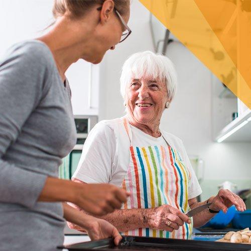 Eine junge Frau steht mit einer älteren Dame in der Küche und hilft beim Kochen.