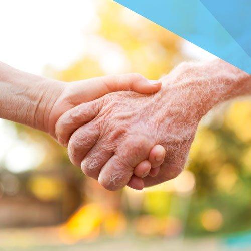 Eine junge Hand hält eine ältere Hand.