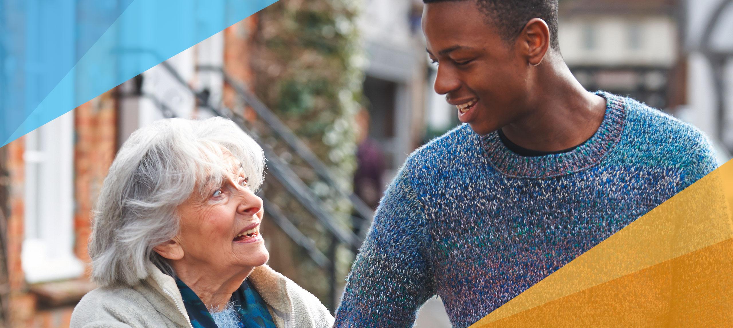 Ein junger Mann mit dunkler Hautfarbe hilft einer älteren Frau beim Tragen des Einkaufs
