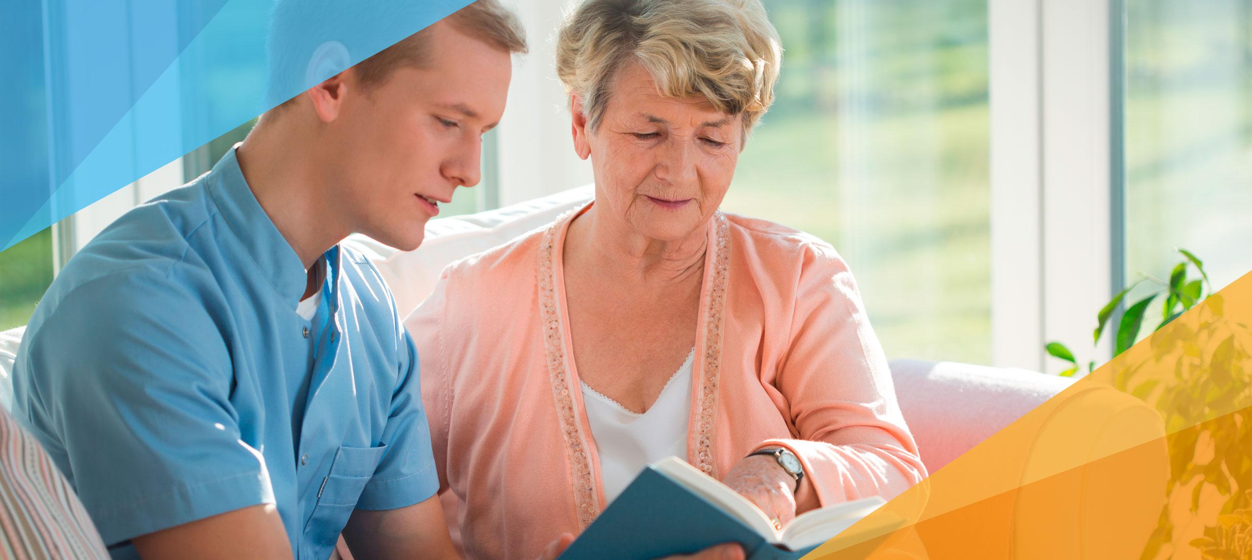 Ein junger Mann hilft einer älteren Dame beim Lesen.
