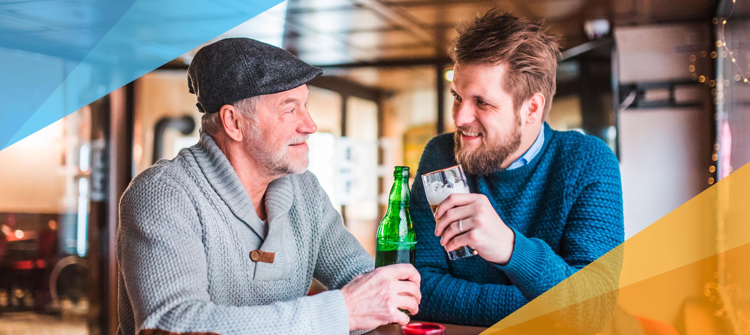 Ein älterer Herr trinkt mit einem Mann um die 30 in einer Kneipe ein Bier.